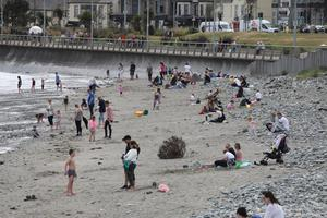 People take to the beach in Newcastle during the warm weather. Photo by Peter Morrison