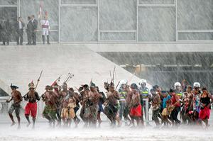 Brazilian natives dance in the rain in front of the Planalto Palace in Brasilia during a demonstration as part of the National Mobilization Week in demand of their rights, on April 14, 2015. Several Brazilian tribes are taking part in the so-called Free Land camp.  AFP/Getty Images