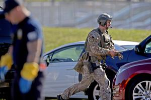 A law enforcement officer rushes toward Marjory Stoneman Douglas High School following a shooting at the school in Parkland, Fla., on Wednesday, Feb. 14, 2018. (John McCall/South Florida Sun-Sentinel via AP)