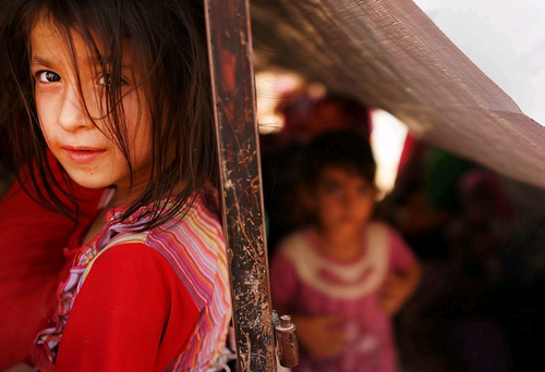 An Iraqi child waits with her family to get into a temporary displacement camp for Iraqis caught-up in the fighting in and around the city of Mosul on June 26, 2014 in Khazair, Iraq. (Photo by Spencer Platt/Getty Images)