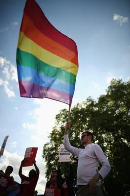 LONDON, ENGLAND - JUNE 03:  A proponent of same sex marriage waves a flag during a vigil outside the Houses of Parliament on June 3, 2013 in London, England.  A government bill allowing same sex marriage in England and Wales was passed in the House of Commons last month, despite the opposition of 133 Conservative MP's. The bill is currently being debated in the House of Lords.  (Photo by Dan Kitwood/Getty Images)