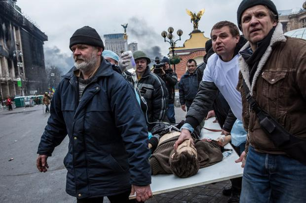 KIEV, UKRAINE - FEBRUARY 20: People carry a wounded anti-government protester to a waiting ambulance on February 20, 2014 in Kiev, Ukraine. After several weeks of calm, violence has again flared between anti-government protesters and police, with dozens killed. (Photo by Brendan Hoffman/Getty Images)