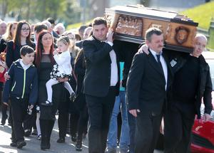 Funeral of Michael McGibbon, who was murdered in Ardoyne in north Belfast last Friday.  The 33-year-old father was shot in a punishment style shooting dying from his wounds later in hospital.  Michael McGibbon's wife Joanne and his children follow his coffin as it leaves the family home on the Crumlin Road for Requiem Mass in Holy Cross Church near by.   Picture by Jonathan Porter/PressEye