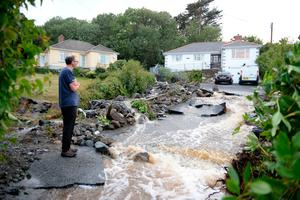 A man looks at a damaged driveway  caused by water from flash flooding in the coastal village of Coverack in Cornwall.  Ben Birchall/PA Wire