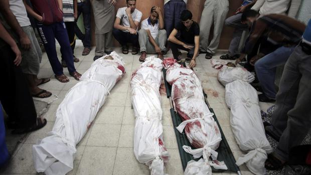 Palestinians grieve over the bodies of their relatives killed in an Israeli strike at a U.N. school in the Jebaliya refugee camp, at the Kamal Adwan hospital in Beit Lahiya, northern Gaza Strip, Wednesday, July 30, 2014. (AP Photo/Khalil Hamra)