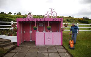 A man cuts the grass beside a bus stop painted pink in preparation for the Giro d'Italia in Cushendall,  Northern Ireland, Tuesday May 6, 2014. Many towns and villages across Ireland have been going pink in preparation for the Giro d'Italia which has three stages in Ireland running from May 9-11.  (AP Photo/Peter Morrison)