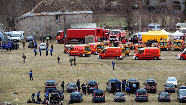 French emergency services workers (back) and members of the French gendarmerie gather in Seyne, south-eastern France, on March 24, 2015, near the site where a Germanwings Airbus A320 crashed in the French Alps.