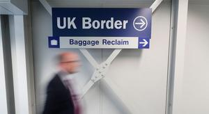 A man walks past a UK Border sign at Belfast International Airport which reopens on Monday June 15th. PA Photo.  Niall Carson/PA Wire