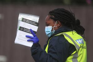 Staff hand out self-test kits at a coronavirus testing centre in Bolton (Danny Lawson/PA)