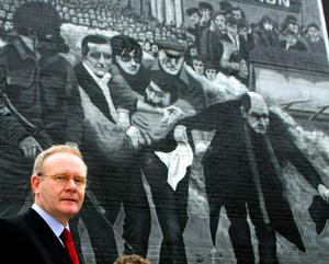 File photo dated 05/11/03 of Martin McGuinness walking past a Bloody Sunday mural in the Bogside in Londonderry.  Paul Faith/PA Wire