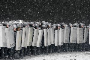 Police prepare to clash with protesters in central Kiev, Ukraine, Wednesday, Jan. 22, 2014. Three people have died in clashes between protesters and police in the Ukrainian capital Wednesday, according to medics on the site, in a development that will likely escalate Ukraine's two month-long political crisis. The mass protests in the capital of Kiev erupted after Ukrainian President Viktor Yanukovych spurned a pact with the European Union in favor of close ties with Russia, which offered him a $15 billion bailout. (AP Photo/Efrem Lukatsky)