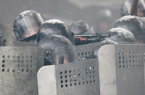 A police officer aims his shotgun during clashes with protesters in central Kiev, Ukraine, Wednesday, Jan. 22, 2014. Three people have died in clashes between protesters and police in the Ukrainian capital Wednesday, according to medics on the site, in a development that will likely escalate Ukraine's two month-long political crisis. The mass protests in the capital of Kiev erupted after Ukrainian President Viktor Yanukovych spurned a pact with the European Union in favor of close ties with Russia, which offered him a $15 billion bailout. (AP Photo/Efrem Lukatsky)