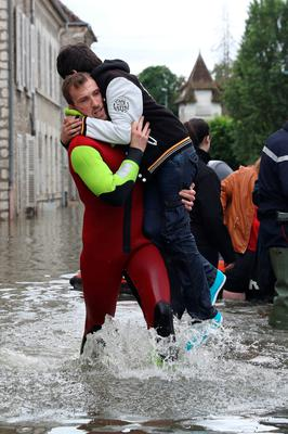 A rescuer evacuates a boy accross a flooded street on June 1, 2016 in Souppes-sur-Loing, southeast of Paris. Torrential downpours have lashed parts of northern Europe in recent days, leaving four dead in Germany, breaching the banks of the Seine in Paris and flooding rural roads and villages.   AFP PHOTO / KENZO TRIBOUILLARDKENZO TRIBOUILLARD/AFP/Getty Images