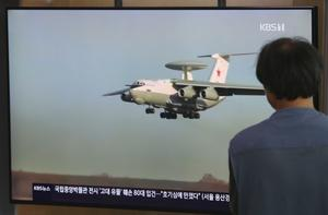 A man watches a TV showing a file image of Russian A-50 airborne early warning and control aircraft during a news programme at the railway station in Seoul (Ahn Young-joon/AP)
