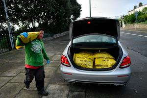 "A man loads the boot of a car with sandbags to protect homes on the Dublin Bay coast on the outskirts of Dublin on October 16, 2017 as Ireland braces for the passing of the storm Ophelia. Schools were closed on October 16 as Ireland braced for an ""unprecedented storm"", with authorities warning that violent winds, rain and storm surges could pose a risk to life. Ophelia, the largest hurricane ever recorded so far east in the Atlantic Ocean, was downgraded to a storm before it hit the Irish coast but the Met Eireann national weather service warned people to remain indoors.  / AFP PHOTO / Ben STANSALLBEN STANSALL/AFP/Getty Images"