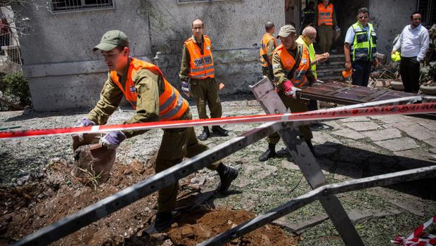 "ASHDOD, ISRAEL - JULY 15:  Homefront Command members clean up rubble from a home after a Hamas rocket landed in the front yard on July 15, 2014 in Ashdod, Israel.  As operation 'Protective Edge"" enters it's eighth day of airstrikes by the Israel Defense Forces (IDF) across the Gaza Strip, Egypt has this morning tabled a ceasefire agreement proposing a halting of fighting starting at 9am. Once violence has ceased, the proposal calls for Israel to open a border crossing into Gaza to allow the movement of goods and people. Israel has accepted the Egyptian proposal for a truce, however it is thought Hamas has rejected the deal.  (Photo by Andrew Burton/Getty Images)"