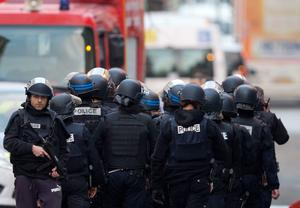 A special intervention unit moves towards the scene in Paris suburb Saint-Denis, Wednesday, Nov. 18, 2015. Explosions and gunfire rang out early Wednesday as heavily armed police surrounded a suburban Paris apartment in a raid targeting the suspected mastermind of last week's Paris attacks. At least two people were killed and two arrested. (AP Photo/Peter Dejong)