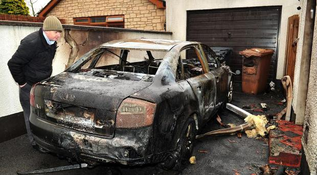 Willie Frazer examines the gutted remains of his car on Sunday