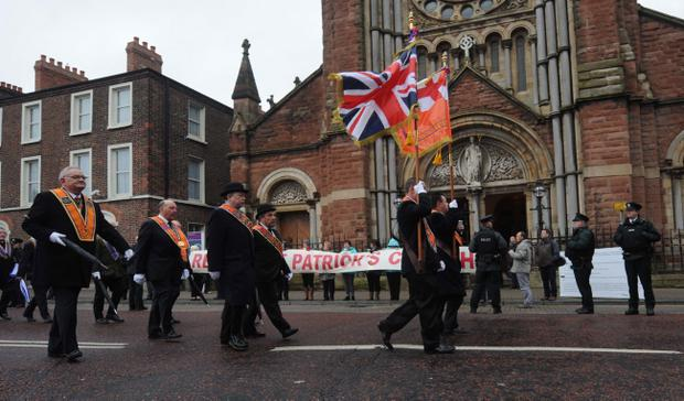 Protesters outside St Patrick's Church in Belfast as a parade passes by