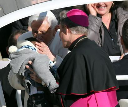 Pope Benedict XVI kisses a baby handed up to him by his secretary George Ganswein as he greets pilgrims in St. Peter's Square at the Vatican Wednesday, Feb. 27, 2013 for the final time before retiring, waving to tens of thousands of people who have gathered to bid him farewell. Benedict was driven around the square in an open-sided vehicle, surrounded by bodyguards. (AP Photo/Luca Bruno)