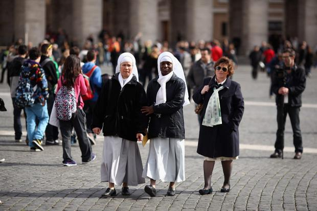 VATICAN CITY, VATICAN - MARCH 12: Nuns walk through St Peter's Square on March 12, 2013 in Vatican City, Vatican. Pope Benedict XVIÄôs successor is being chosen by the College of Cardinals in Conclave in the Sistine Chapel. The 115 cardinal-electors, meeting in strict secrecy, will need to reach a two-thirds-plus-one vote majority to elect the 266th Pontiff. (Photo by Dan Kitwood/Getty Images)