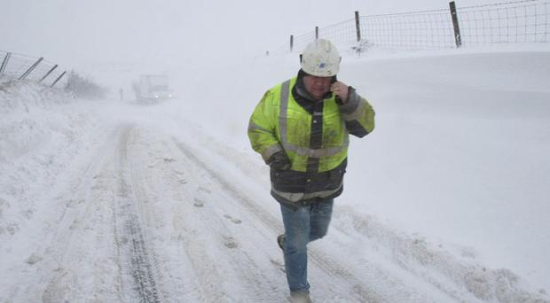 A Northern Ireland Electricity engineer as heavy snow falls on the Carnlough to Ballymena