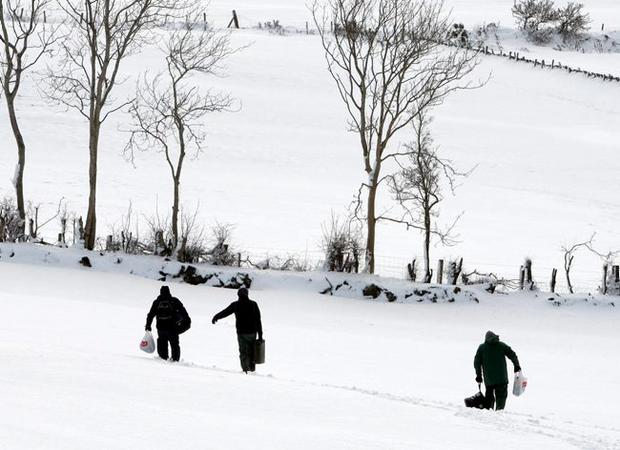 Locals take to the fields, off the main road to Feystown, above Glenarm in Co Antrim, due to unpassable snow drifts