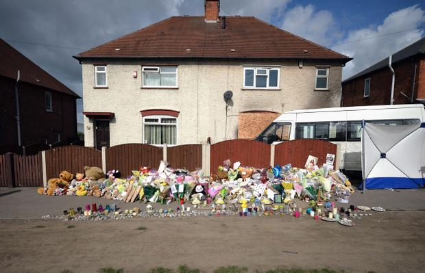 Floral tributes adorn the pavement outside a house in Allenton following the fire which claimed the lives of six children on May 14, 2012 in Derby, England