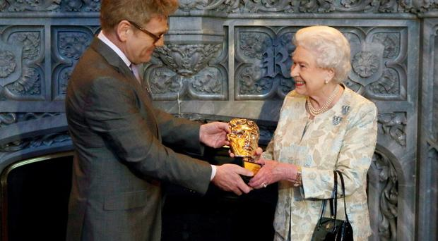 Queen Elizabeth II receives an honorary BAFTA from Belfast's Kenneth Branagh in recognition of a lifetime's support to British Film and Television at Windsor Castle