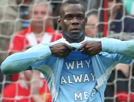 Mario Balotelli reveals his now famous 'why always me' t-shirt during Manchester City's 6-1 destruction of Manchester United