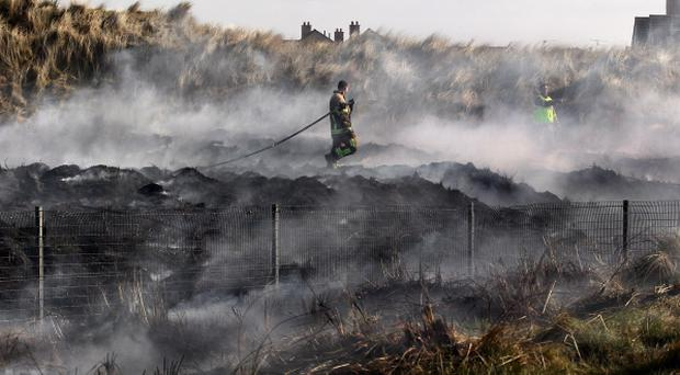 Fire crews tackle a blaze in Portrush which broke out among sand dunes within the grounds of Portrush golf clubs