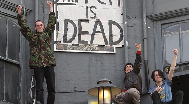 People cheer in front of a banner displaying the message 'The Witch is Dead' as they celebrate the death of former British Prime Minister Margaret Thatcher in Brixton on April 8, 2013
