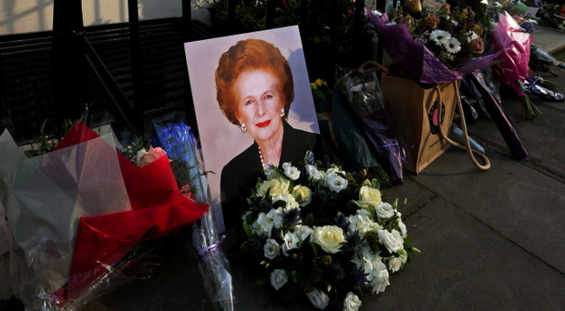A portrait of former Prime Minister Margaret Thatcher is left next to floral tributes outside her residence in Chester Square, London
