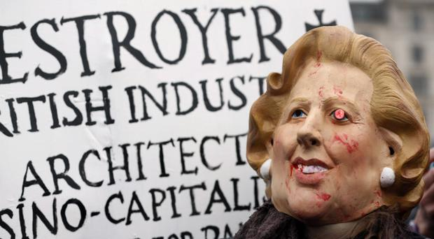 A protester wears a mask depicting former British Prime Minister Margaret Thatcher during a party to mark her death in central London's Trafalgar square, Saturday, April 13, 2013