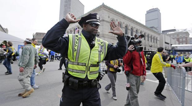 A Boston police officer clears Boylston Street following an explosion at the finish line of the 2013 Boston Marathon in Boston, Monday, April 15, 2013. Two explosions shattered the euphoria at the finish line on Monday, sending authorities out on the course to carry off the injured while the stragglers were rerouted away from the smoking site of the blasts. (AP Photo/Charles Krupa)
