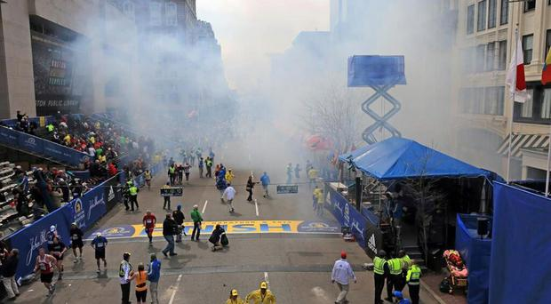 Medical workers aid injured people at the 2013 Boston Marathon following an explosion in Boston, Monday, April 15, 2013
