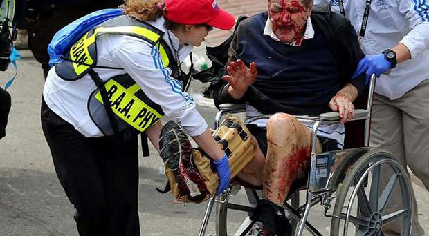 Medical workers aid an injured man at the 2013 Boston Marathon following an explosion in Boston, Monday, April 15, 2013.