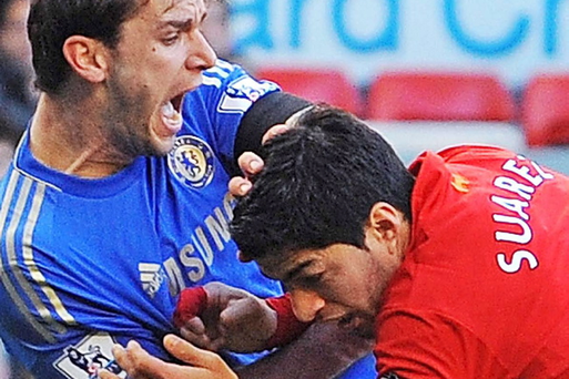 Liverpool's Luis Suarez (R) clashes with Chelsea's Serbian defender Branislav Ivanovic (L) after appearing to bite the player during the Premier League match between Liverpool and Chelsea at Anfield
