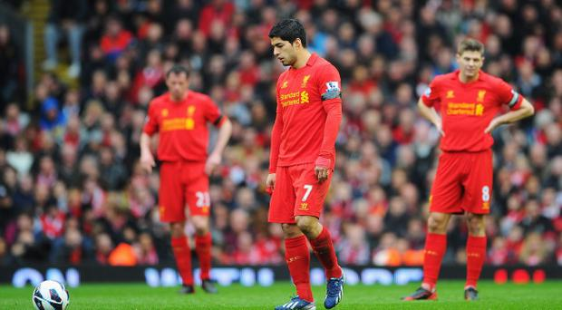 LIVERPOOL, ENGLAND - APRIL 21: Luis Suarez of Liverpool looks dejected with team mates after the opening goal by Oscar of Chelsea during the Barclays Premier League match between Liverpool and Chelsea at Anfield on April 21, 2013 in Liverpool, England. (Photo by Michael Regan/Getty Images)