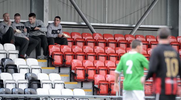 Cliftonville players including Joe Gormley and Ryan Catney enjoy a fish supper from the empty Cliftonville fans stand during this evenings Danske Bank Irish Premiership league game between Crusaders and Cliftonville at Seaview, Belfast