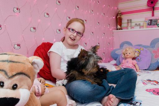 Nicole McBride (10) and her dog Evea in her new bedroon at home in Derry. Picture Martin McKeown