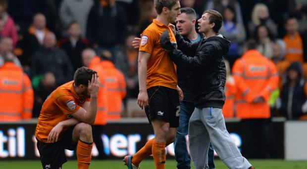 WOLVERHAMPTON, ENGLAND - APRIL 27: Kevin Doyle is confronted by fans as team-mate Roger Johnson of Wolverhampton Wanderers looks dejected at the end of the npower Championship match between Wolverhampton Wanderers and Burnley at Molineux on April 27, 2013 in Wolverhampton, England. (Photo by Shaun Botterill/Getty Images)