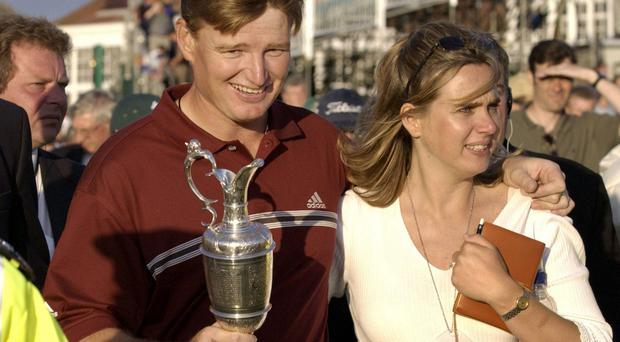 Ernie Els, left, of South Africa, walks off the 18th hole holding the Claret Jug with his wife Leizel Els, right, after winning The 131st Open Championship at Muirfield, Scotland