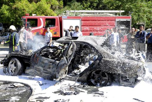 This photo released by the Syrian official news agency SANA, shows Syrians inspecting a damaged car at the scene of a car bomb exploded in the capital's western neighborhood of Mazzeh, in Damascus, Syria, Monday, April. 29, 2013