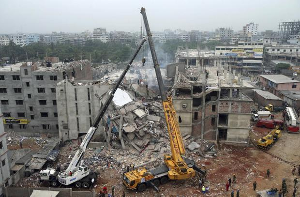 The garment factory building collapsed on Wednesday, is seen from a building nearby as a crane prepares to lift the fallen ceiling, in Savar, near Dhaka, Bangladesh, Monday April 29, 2013