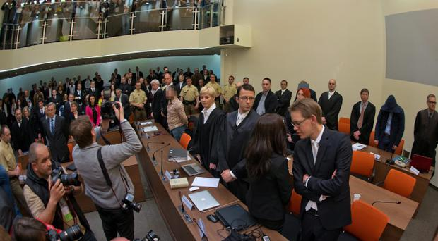 Defendant Beate Zschaepe stands in court with her legal team, lawyers Wolfgang Heer, Anja Sturm and Wolfgang Stahl, on the first day of the NSU neo-Nazi murder trial on May 6, 2013 in Munich, Germany