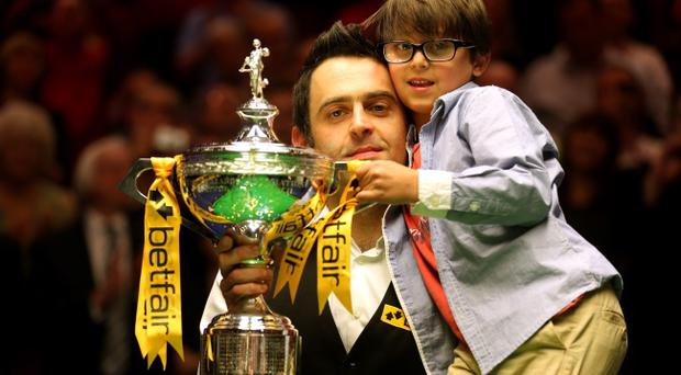 SHEFFIELD, ENGLAND - MAY 06: Ronnie O'Sullivan of England poses with the trophy and his son Ronnie after beating Barry Hawkins of England to win the Betfair World Snooker Championship at the Crucible Theatre on May 6, 2013