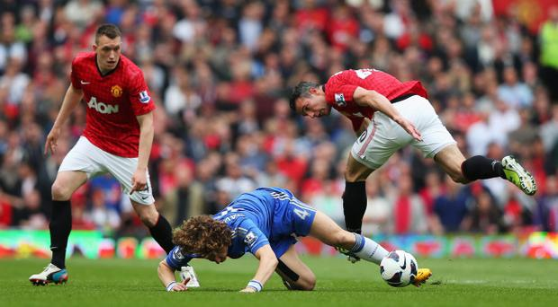 MANCHESTER, ENGLAND - MAY 05: Robin van Persie of Manchester United challenges David Luiz of Chelsea watched by team mate Phil Jones (L) during the Barclays Premier League match between Manchester United and Chelsea at Old Trafford on May 5, 2013 in Manchester, England. (Photo by Alex Livesey/Getty Images)