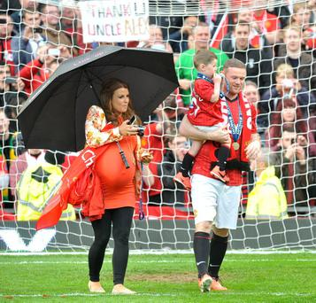 A heavily pregnant Coleen Rooney with husband Wayne Rooney and their son Kai, on the pitch to celebrate Manchester United winning the Barclays Premier League