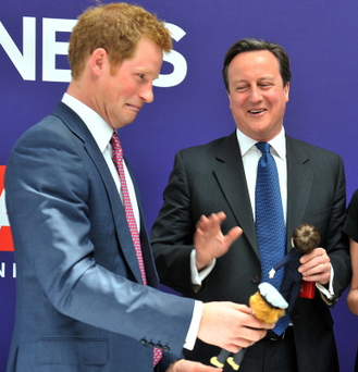 Prince Harry and British Prime Minster David Cameron are presented with dolls of themselves by 'Makielab' company co-founder Jo Roach (R) during part of a UK business campaign called 'GREAT' at the Milk Studios on May 14, 2013 in Manhattan, New York.
